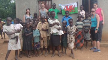 YFC visitors outside house on Kamuli land with community children